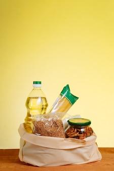 Различная еда в бумажном пакете на деревянном столе, на желтом фоне