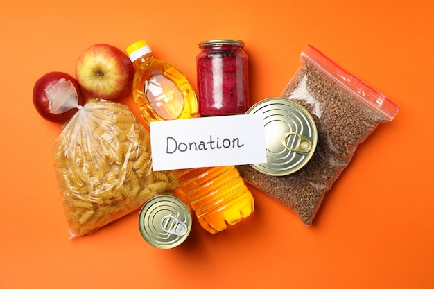 Different food on orange space, top view. donation concept