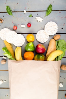 Different food in paper bag on wooden background