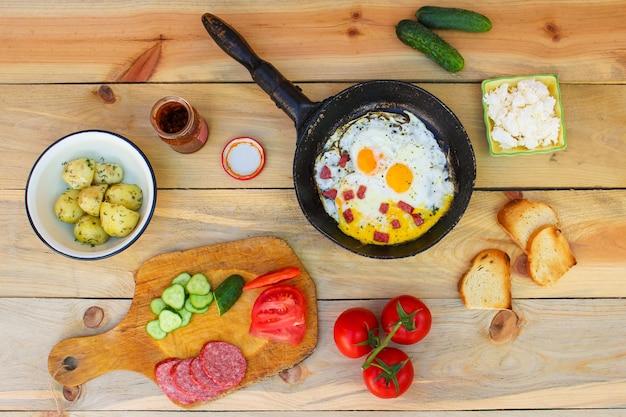 Разная еда: яичница на сковороде, вареный картофель, творог, гренки, редис, огурцы, помидоры, копченая колбаса, мята, щавель на деревянном столе. вид сверху.