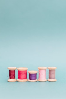 Different forms one content the concept  personality uniqueness. multi-colored threads spools  on a blue sewing needlework embroidery handmade top viewconcept flat lay different differing