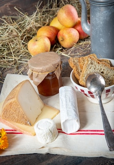 Different french cheeses with apples on straw