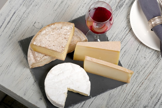 Different french cheeses with a glass of wine
