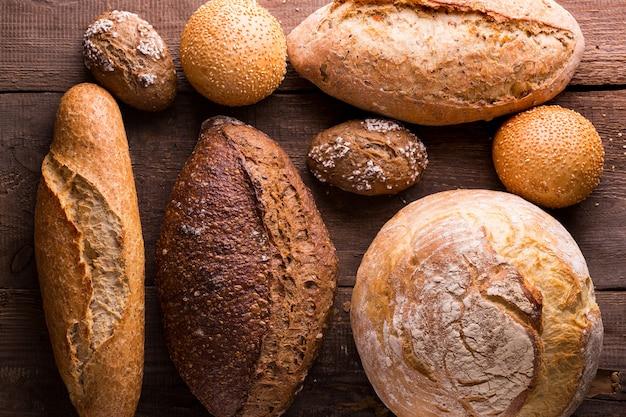 木製のテーブルにさまざまな焼きたてのパンとパン