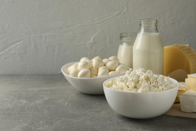 Различные свежие молочные продукты на сером фоне, место для текста