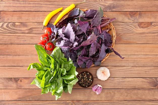 木製のテーブルに野菜とスパイスとさまざまな新鮮なハーブ