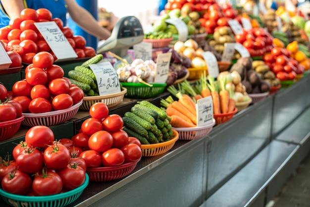 Различные свежие овощи в корзинах на прилавке.