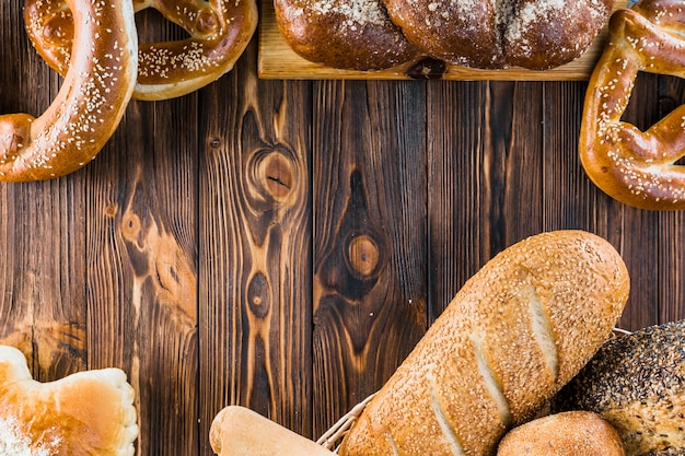 Different freshly baked bread on the wooden background