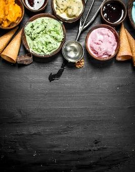黒い黒板にワッフルカップが付いているボウルのさまざまなフルーツアイスクリーム