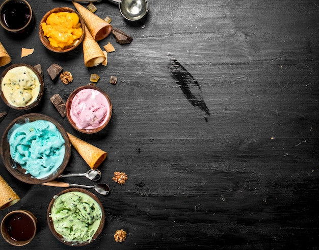 ワッフルカップのボウルにさまざまなフルーツアイスクリーム。黒い黒板に。