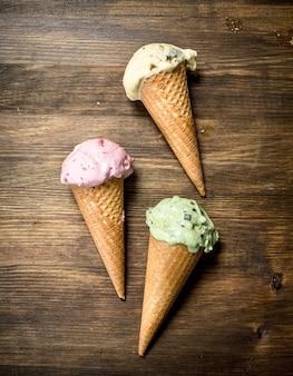 Различное фруктовое мороженое в вафельных стаканчиках на деревянном столе