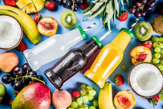 Different fruit juices smoothies concept summer vitamins diet with tropical fruits and berries on a light background