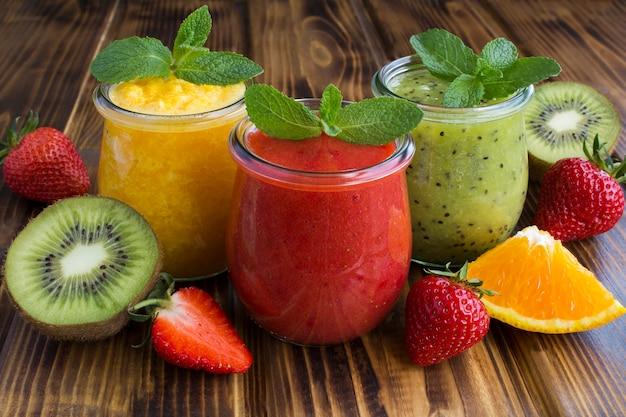 木製の背景の小さなガラスの瓶にさまざまなフルーツのスムージーまたはピューレ。閉じる。