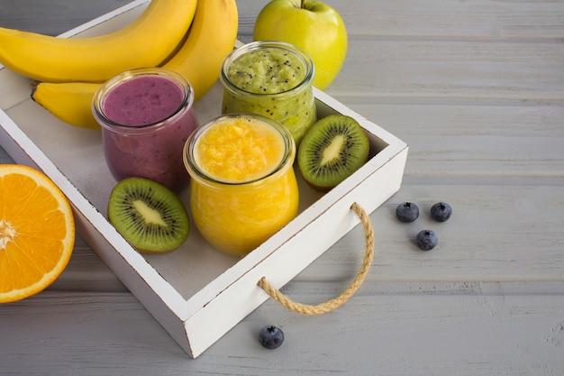 さまざまなフルーツのスムージーや灰色の木製の白いトレイに小さなガラスの瓶にピューレ