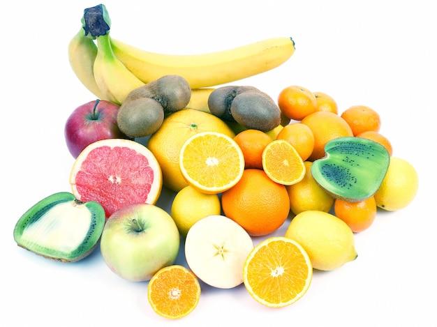 全体と白い背景にスライスしたさまざまな果物。健康的な新鮮な野菜と食品