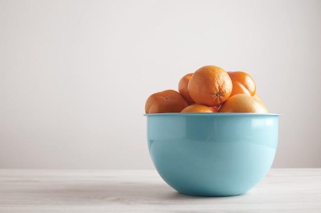 側面から白い木製のテーブルの空白の壁の前に大きな金属製の青いボウルにさまざまな果物と柑橘類