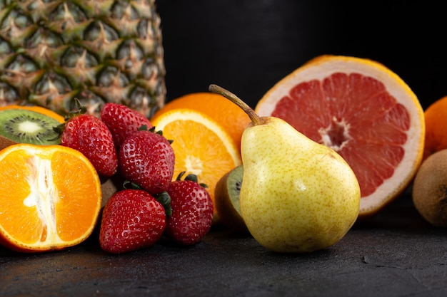 Different fruits fresh ripe mellow juicy half cut isolated on dark desk
