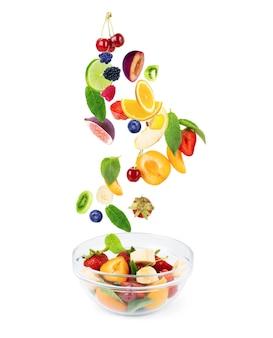 Различные фрукты, в полете летят в тарелку с фруктами, на белом фоне