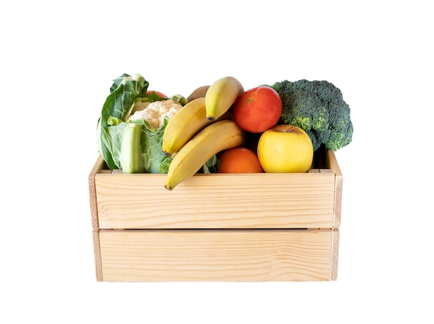 Different fruits and vegetables in wooden crate, isolated on white