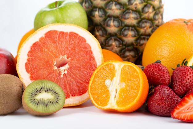 Различные фрукты, богатые витаминами, свежие спелые, сочные, изолированные на белом полу