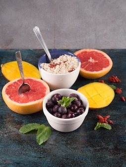 Different fruits with oatmeal on table