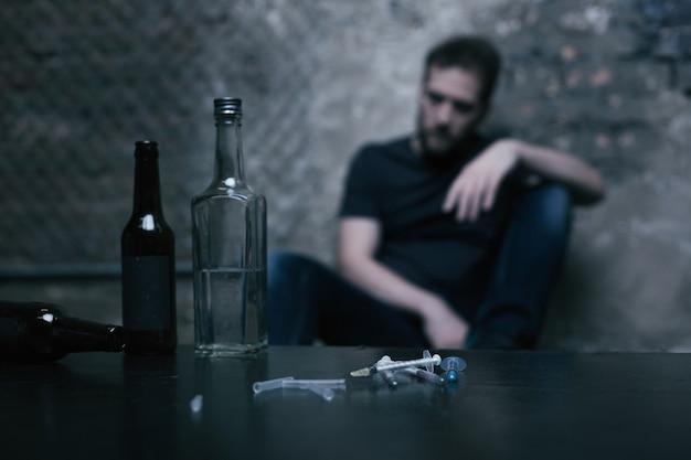 마약 중독자가 앉아있는 동안 중고 주사기 옆 차고의 테이블에있는 다른 전체 큰 병
