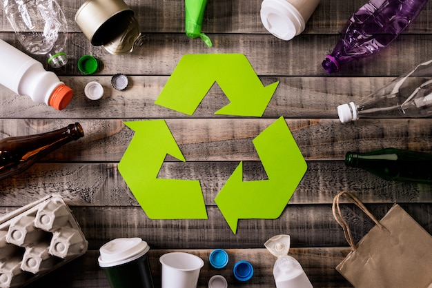 Different garbage materials with recycling symbol on table background.