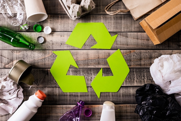 Different garbage materials with recycling symbol on table background