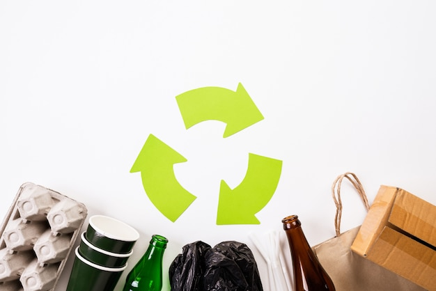 Different garbage materials with recycling symbol on white background