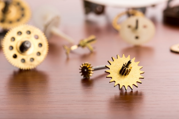 Different gears on the wooden table closeup