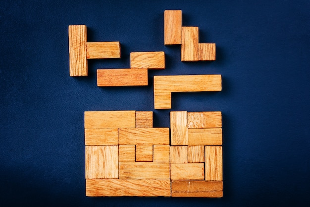 Different geometric shapes wooden blocks arrange in solid figure on a dark background.