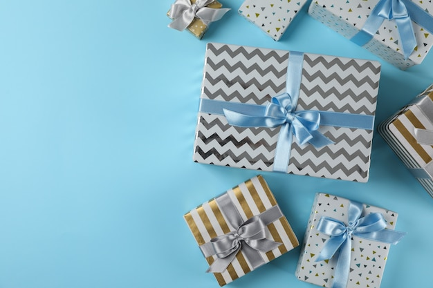 Different gift boxes on blue background, copy space