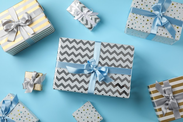 Different gift boxes on blue background, top view