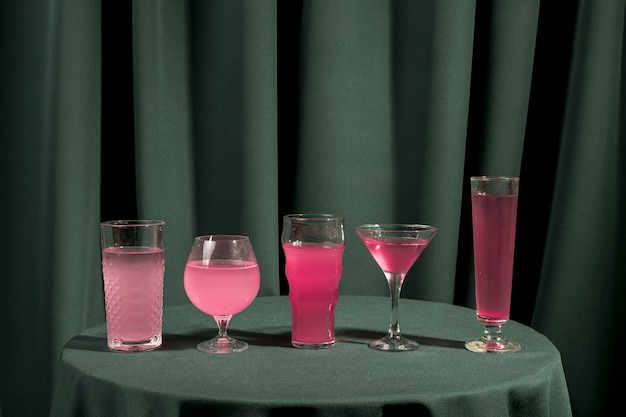 Different glasses filled with pink liquid on table