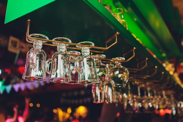 Different glasses hanging over the bar. soft focus.