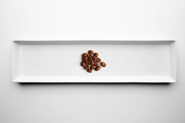 Diversi gradi di torrefazione professionale artigianale caffè isolato su piastra bianca, vista dall'alto