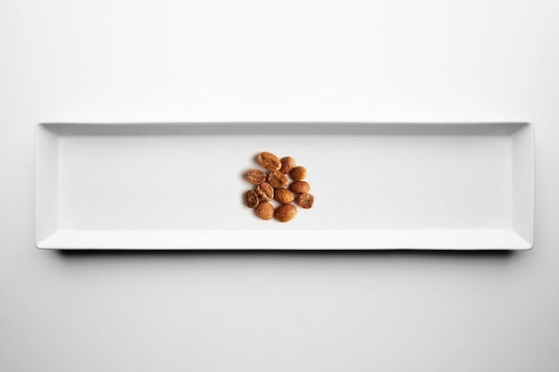 Different grades of artisan professional roasting coffee isolated on white plate, top view