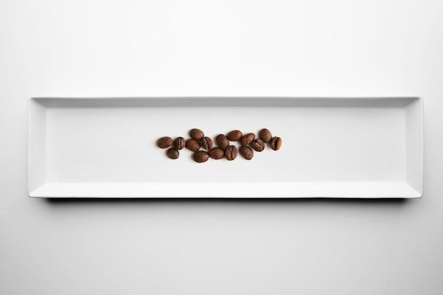 Различные сорта ремесленника профессиональной обжарки кофе, изолированные на белой тарелке, вид сверху