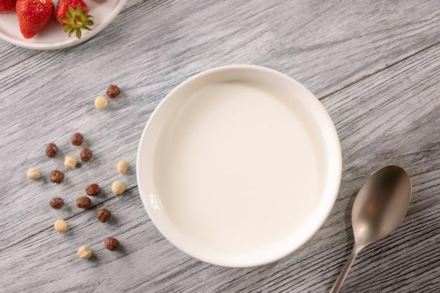다른 곡물 공 및 복사 공간이 회색 나무 테이블에 우유와 잘 익은 딸기 한 접시. 아침 식사. 평면도