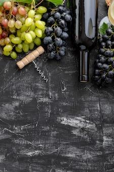 黒の背景に異なるブドウの種類のワインボトルとコルク栓抜きフラットレイフレーム。