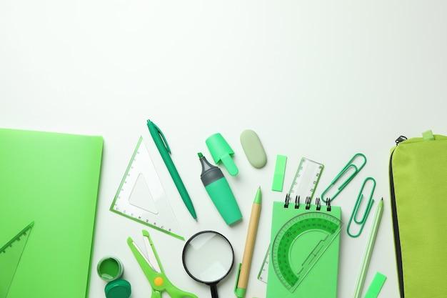 Различные зеленые канцелярские товары на белом фоне, место для текста