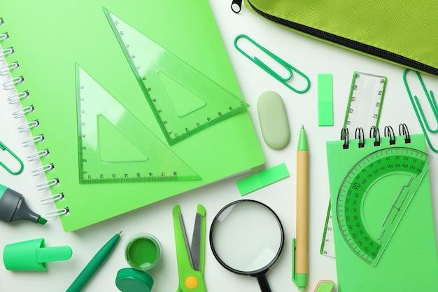 Различные зеленые канцелярские товары на белом фоне, вид сверху