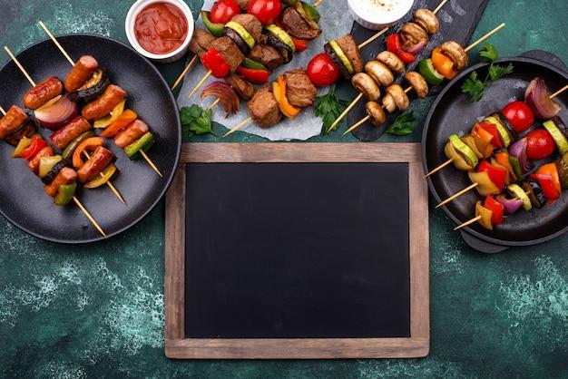 Разные шашлыки-гриль с мясом, грибами, сосисками и овощами на шпажках