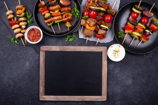 꼬치에 고기, 버섯, 소시지 및 야채를 곁들인 다양한 구운 케밥