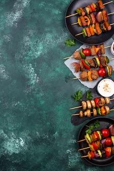 串に刺した肉、マッシュルーム、ソーセージ、野菜のさまざまなグリルケバブ