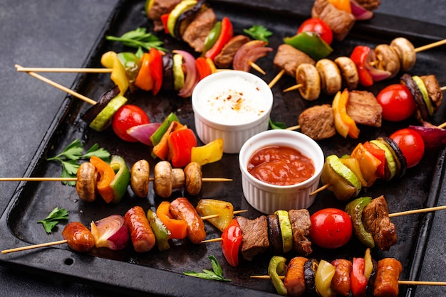 Different grilled kebabs with meat, mushrooms, sausages and vegetable on skewers