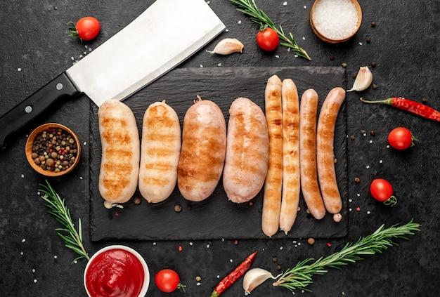 Различные жареные колбаски со специями и розмарином, поданные на разделочной доске на каменном фоне с местом для текста