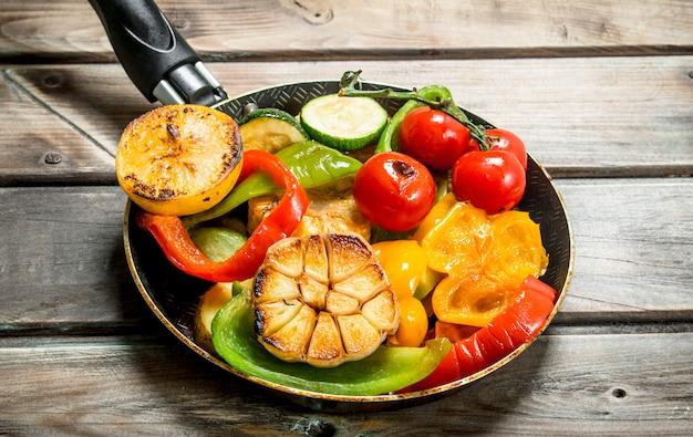 木製のテーブルにハーブとスパイスを添えたさまざまなグリル野菜。