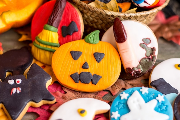Different halloween cookies on table with autumnal leaves
