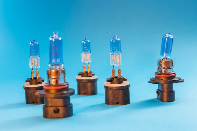 Different halogen auto glass bulb isolated on blue background. vechile light lamp for use in illumination when moving.